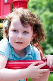 Young girl having fun outside at park on a playground swing set Royalty Free Stock Images