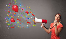 Young girl having fun, shouting into megaphone with balloons Stock Image