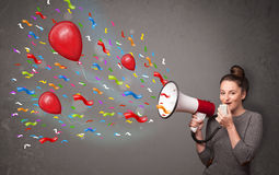 Young girl having fun, shouting into megaphone with balloons Stock Photos