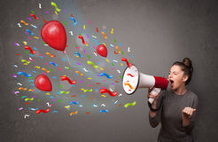 Young girl having fun, shouting into megaphone with balloons. And confetti Royalty Free Stock Photo