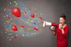 Young girl having fun, shouting into megaphone with balloons Royalty Free Stock Images