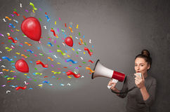 Young girl having fun, shouting into megaphone with balloons Royalty Free Stock Photos