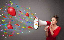 Young girl having fun, shouting into megaphone with balloons Stock Photography