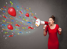 Young girl having fun, shouting into megaphone with balloons Royalty Free Stock Photography