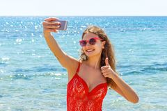 Young girl having fun taking smartphone selfie pictures of herself. travel holidays. happy young woman giving hand sign thumbs up stock photos