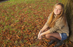 Young girl having fun walks in autumn park. Stock Images
