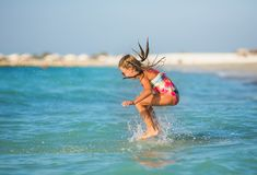 Cute little girl on summer vacation. Young girl having fun in the waves Stock Photos
