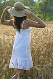 Young girl with hay hat in a wheat field Royalty Free Stock Photo