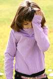 Young Girl Headache. An adorable young Latin American girl in the 5-8 year old age range. She is wearing a pink purple turtleneck and has brown hair glowing in Stock Photo