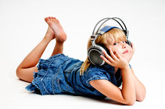 Young girl in headphones. Young girl listen to music in headphones on white background Royalty Free Stock Photo