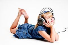 Young girl in headphones. Young girl listen to music in headphones on white background Royalty Free Stock Photos