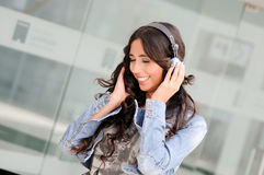 Young girl with headphones. Listening to the music and dancing in the street Royalty Free Stock Photos