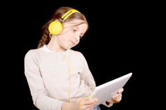 A young girl with headphones and a digital tablet Stock Images