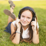 Young girl in headphones enjoys the music lying on the green grass. Pleasure. Stock Photos