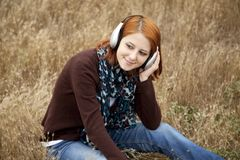 Young girl with headphones at field. Royalty Free Stock Images