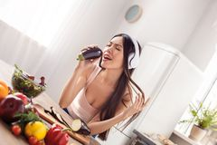 Young girl in headphones at kitchen healthy lifestyle standing listening to music singing song to eggplant stock photos