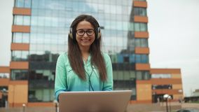 A young girl with headphones and a laptop laughs. stock footage