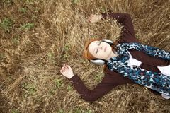 Young girl with headphones lying at field. Stock Photography
