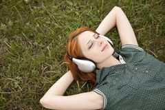 Young girl with headphones lying at green grass. Royalty Free Stock Photography
