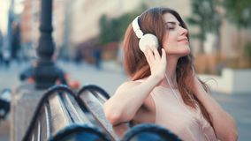 Young girl with headphones outdoors. Young girl with headphones on the bench Stock Photography