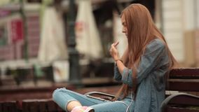 Young girl with headphones and phone sitting on a bench and listening to music. stock video