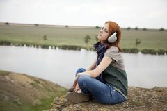 Young girl with headphones at rock Royalty Free Stock Photo