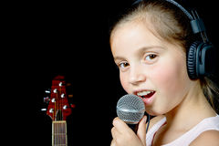 A young girl with headphones singing with a microphone Royalty Free Stock Photos