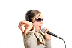 A young girl with headphones singing with a microphone. On white background Stock Photo
