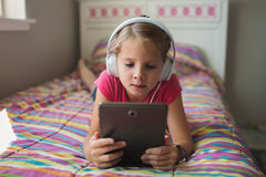 Young girl with headphones and tablet. Young girl lying on the bed with headphones and tablet Stock Images