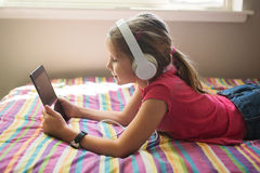 Young girl with headphones and tablet. Young girl lying on the bed with headphones and tablet Royalty Free Stock Photos