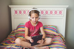 Young girl with headphones and tablet. Young girl sitting on the bed with headphones and tablet Royalty Free Stock Photos