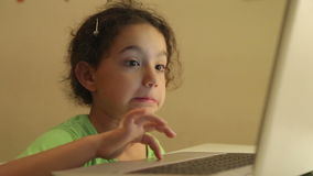Young girl with headphones using computer for homework stock video