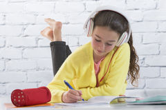Young girl with headset doing homework on floor stock photo