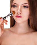 Young girl with healthy skin applying make up on face Royalty Free Stock Photos