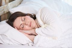 Young girl. Healthy sleep. White bed. Beautiful woman. Brown hair Royalty Free Stock Photography