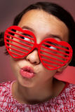 Young girl with heart shaped shutter shades. Blowing a kiss Stock Photo