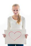 Young girl with the heart on the sheet of paper. Emotional young girl with blond hair in casual clothes holding blank sheet with the heart on it Stock Photos