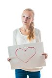 Young girl with the heart on the sheet of paper. Emotional young girl with blond hair in casual clothes holding blank sheet with the heart on it Stock Images