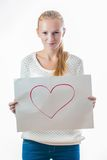 Young girl with the heart on the sheet of paper. Emotional young girl with blond hair in casual clothes holding blank sheet with the heart on it Royalty Free Stock Photo