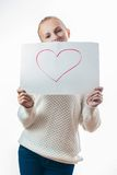 Young girl with the heart on the sheet of paper royalty free stock image