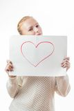 Young girl with the heart on the sheet of paper. Emotional young girl with blond hair in casual clothes holding blank sheet with the heart on it Stock Image