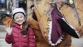 Young girl in helmet posing with man in t rex costume at sidewalk. Cold day, slowmotion stock video footage
