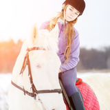 Young girl in helmet riding white horse on field Royalty Free Stock Images
