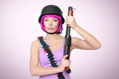 Young girl in helmet with a shotgun Stock Photo