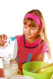 Young girl helping in baking cake. Young girl helping  mummy to bake cake Royalty Free Stock Image