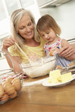 Young Girl Helping Grandmother To Bake Cakes In Kitchen Stock Photo