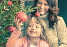 Young girl helping her mother decorating the Christmas tree. Holding some Christmas baubles in her hand Royalty Free Stock Images