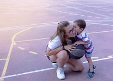 Young girl helping a little boy play basketball and the boy gives her a kiss as a thank you