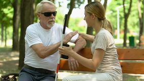 Free Young Girl Helping Mature Blind Man To Seat Down On Bench In Park, Kindness Royalty Free Stock Photos - 157540998