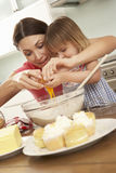 Young Girl Helping Mother To Bake Cakes In Kitchen Royalty Free Stock Photography